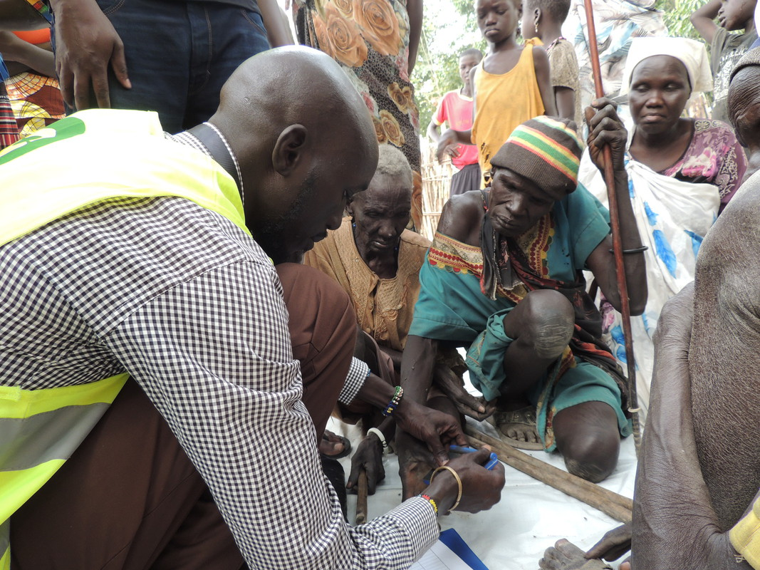 Pedro Marial Rock, miembro del equipo de Oxfam, toma las huellas dactilares a modo de firma de Nyabiey (izquierda) y Nyakonga (derecha) para registrar que recibieron alimentos en la distribución que se llevó a cabo en el 20 de marzo de 2017. Fotografía: L