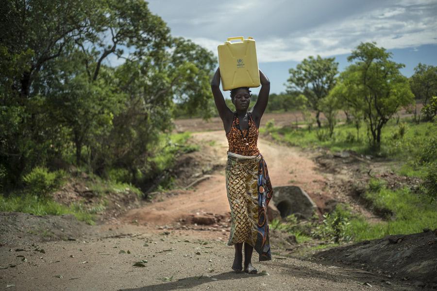 Beatrice llevando agua en el asentamiento de refugiados de Imvepi. Fotografía: Kieran Doherty/Oxfam