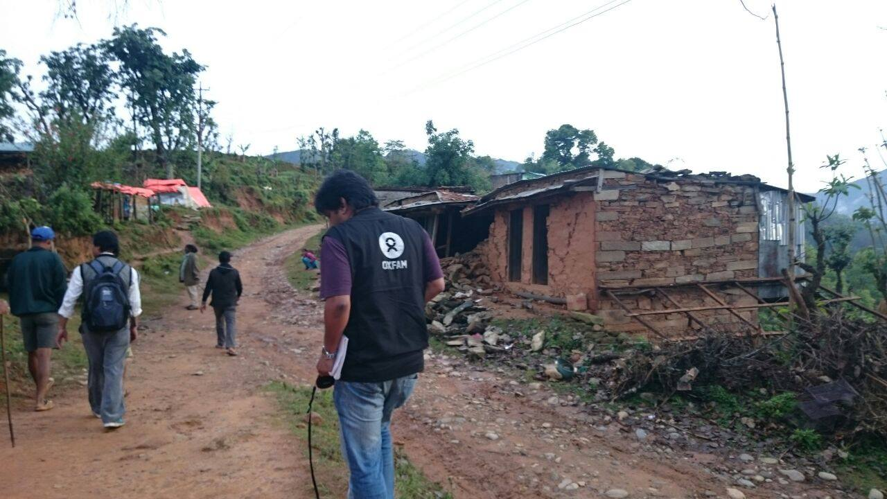 An Oxfam assessment team walks on a dirt path into a village struck by the earthquake.