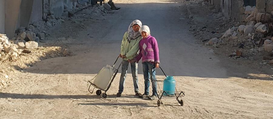 Alaa, 9, and Hayat 11, walk to a public water tank. Photo: Feras Olabi/Oxfam
