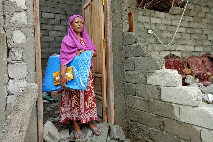 Mas'ad delante de su casa derrumbada cerca de la ciudad de Palu, azotada por el terremoto. Ella ha recibido un refugio de emergencia de Oxfam. Foto: Irwan Firdaus/Oxfam