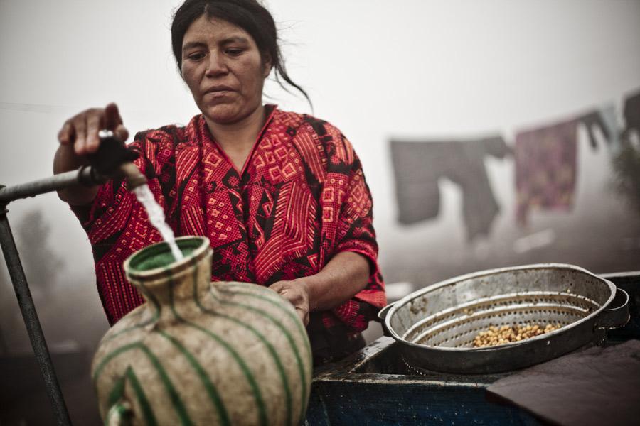 Maria Guachiac, agricultora de la comunidad de PAcutan II, limpia maíz en un punto de abastecimiento de agua. Foto: Pablo Tosco/Oxfam