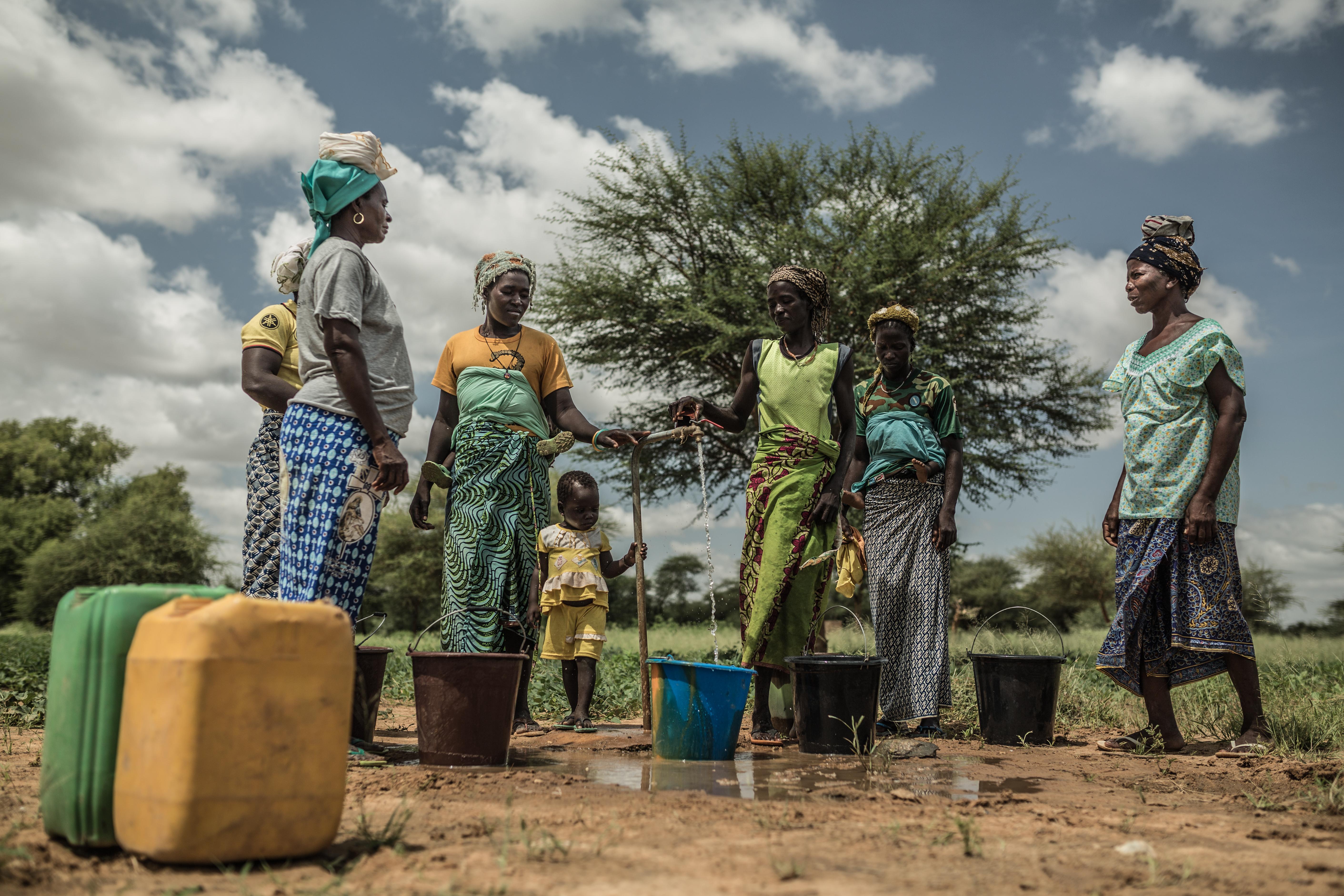 Noaga Ouèda (à droite), avec d'autres femmes de son village, prend de l'eau potable à un robinet alimenté par le château d'eau installé dans son village et qui fonctionne à l'énergie solaire.