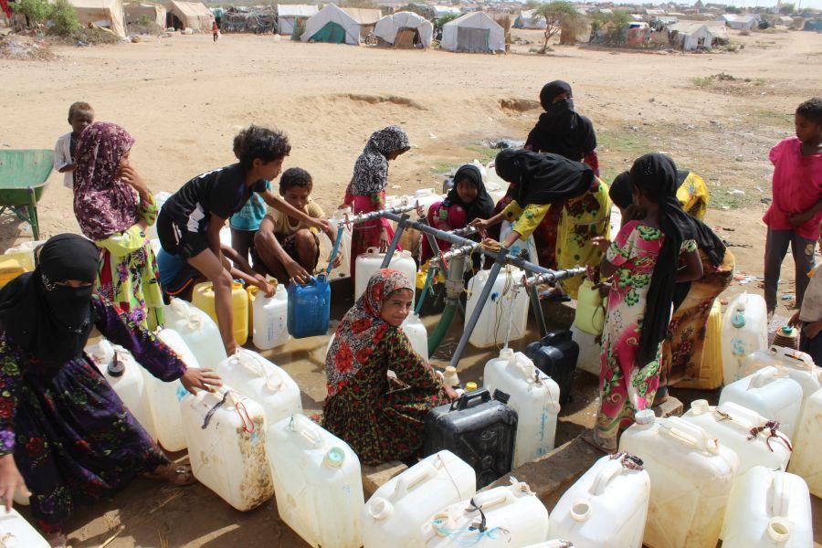 Des déplacés font des réserves d'eau à un point de distribution installé par Oxfam dans le camp de Al-Manjorah, au Yémen.