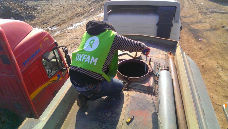 Un bénévole d'Oxfam vérifie l'eau transportée par camion avant de la pomper vers le réservoir d'eau principal de Herjalleh, au sud de Damas.