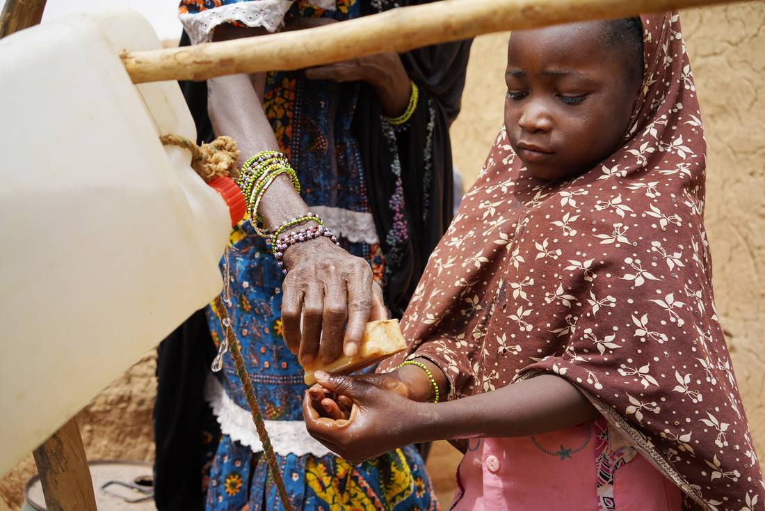 Maimouna – her daughter Lehana * (5) demonstrate the hand washing skills they've learned 'second hand' in the village, Kokosseye, Ouallum district, Niger, March, 2015. Photo credit: Abbie Trayler-Smith/Oxfam