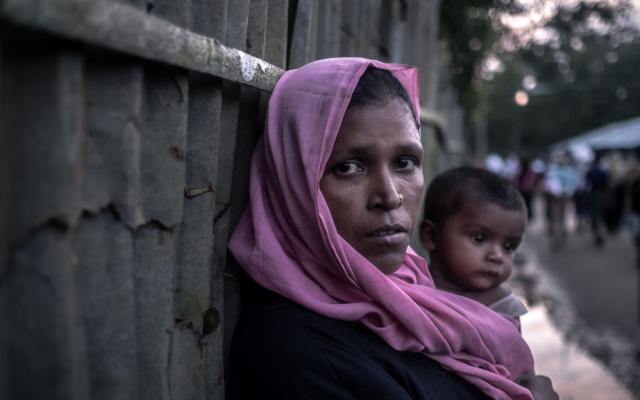 Razida_, 35 carries her ten month old son Anisul through Unchiprang Camp in Bangladesh
