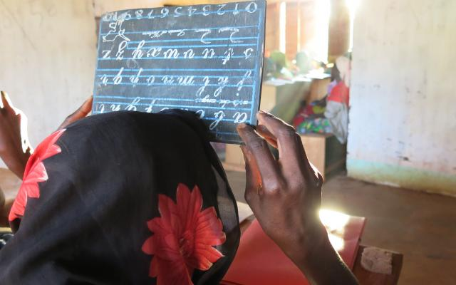 "Fatima* writes the letter ""e"" on a small blackboard, during a literacy lesson at the headquarters of Bria's Women Leaders Association, CAR. Credit: Godet, Oxfam"