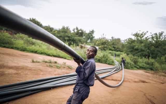 Ndaondi Ruhaliza porte un tuyau en plastique utilisé pour la conduite d'eau à Malinde. Photo : Alexis Huguet/Oxfam