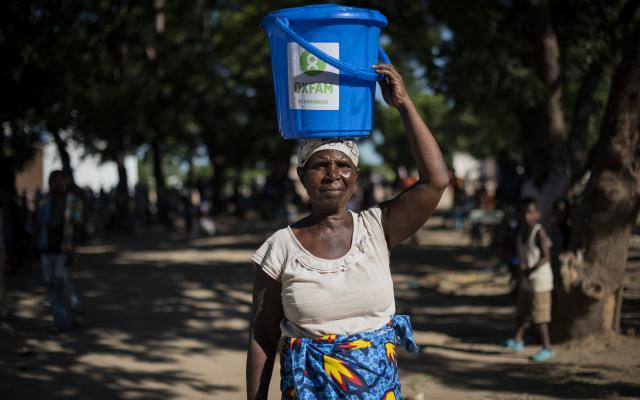 Fainesi, 65, stands with freshly drawn water, stored in her bucket donated by Oxfam, in the Bangula camp, southern Malawi. Fainesi and her family and neighbors had to leave the village of Chikazi after their houses collapsed in the flooding caused by Cyclone Idai. Photo: Philip Hatcher-Moore/Oxfam