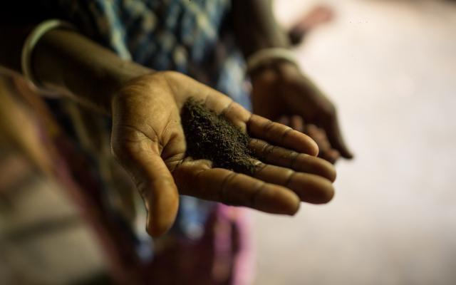 Una mujer muestra la porción de té que las y los trabajadores reciben mensualmente. Photo: Roanna Rahman/Oxfam