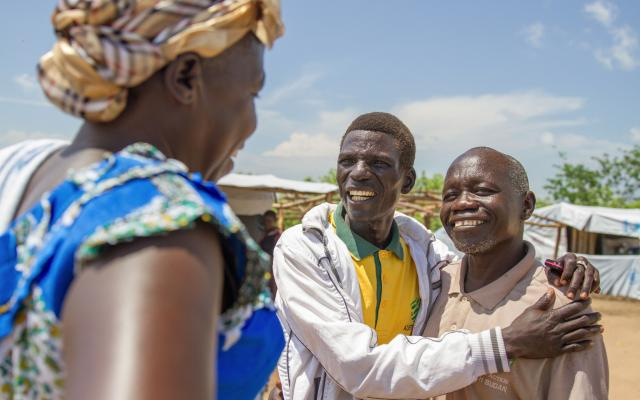 Richard (middle), a refugee and pastor at the Imvepi refugee settlement in Uganda, meets an old friend in the settlement's market. Credit: Coco McCabe/Oxfam