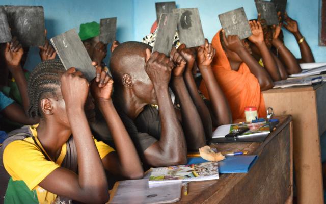 """Supervivientes de violencia aprenden a escribir la letra """"e"""" durante una clase de alfabetización en un hogar para mujeres en Bria, en el corazón de la República Centroafricana. Fotografía: Aurélie Godet/Oxfam"""