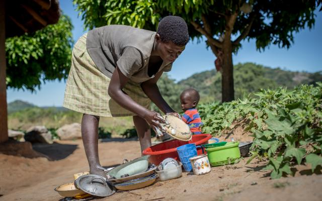 28 year old Edna washes dishes outside her home in Masvingo District, Zimbabwe.
