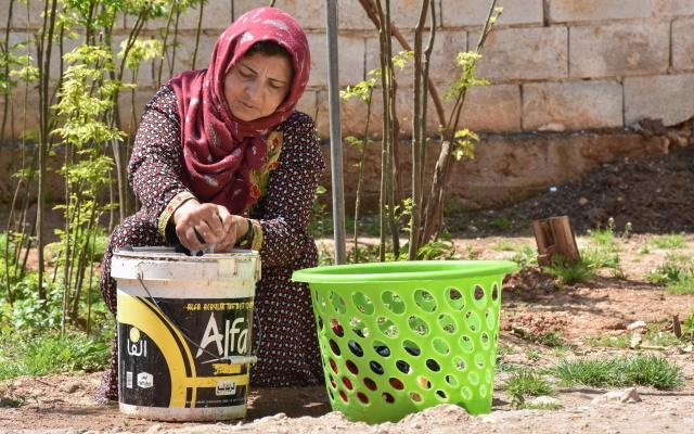 Sarah, 37, single mother of six, washing laundry. On top of her two jobs she cooks, cleans, and cares for her children and is also trying to grow some vegetables in the garden to improve their diet. Photo credit: Islam Mardini/Oxfam