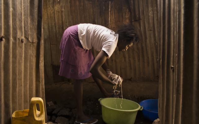 Agnes Adhiambo, 25, domestic worker, washes clothes in Mashimoni village, Mathare, Nairobi, Kenya.