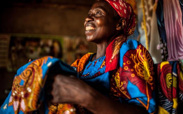 Theresie Nyirantozi (60 yrs) admires tailored fabric she purchased in her home in Kirehe District, Eastern Rwanda.