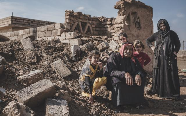 Abu Ahmad sits with his children in the rubble that used to be his home