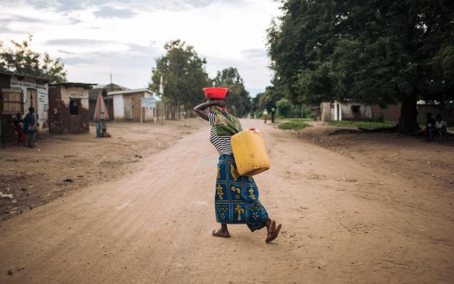 Rizini Furaha carries a water jerrican at dusk in Malinde, DRC.