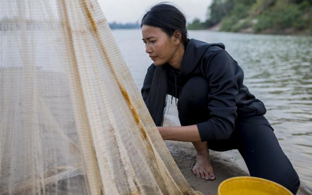Hong Rany (26) checks a net for fish near her home on Chrem Island out in the middle of the Mekong River.