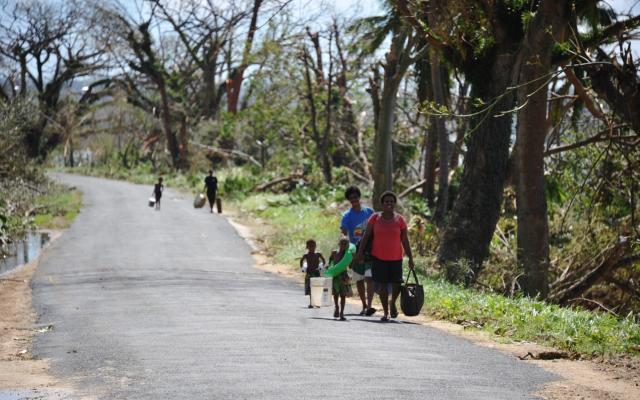 People walking along a road carrying bags