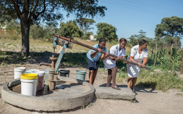 Nurses pump water at Somerton Clinic, Zimbabwe