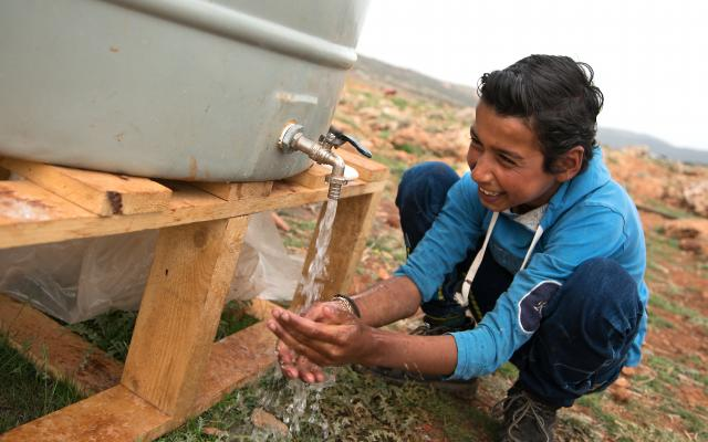A resident of Btedai ITS (Informal tented settlement) washes his hands with water from an Oxfam provided water tank.