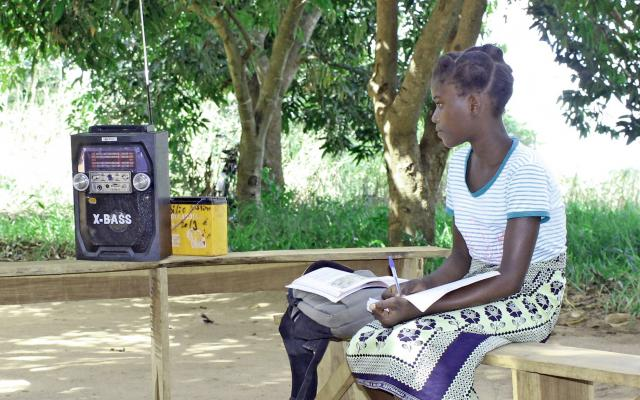 Benedita Matias listens to the voice streaming from the radio she has placed in the shade in front of her, outside the family's house near the town of Mocuba in Mozambique.