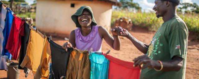 Ulita Mutambo's husband Muchineripi Sibanda helps her hang up laundry outside their home in Ture Village, Zvishevane region, Zimbabwe.  Credit: d'Unienville/Oxfam