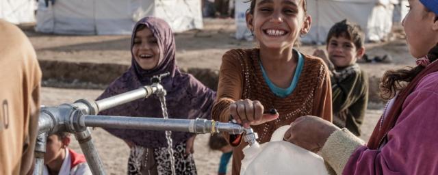 Niños llenan botellas de agua limpia en un puesto de agua en el campamento de Hassansham, Iraq. Crédito: Tegid Cartwright / Oxfam