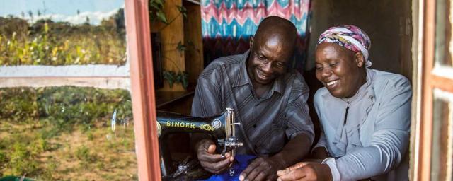 Orpheus Dube enseigne des techniques de couture à son épouse Paulina Sibanda chez eux, au Zimbabwe. Crédit : Aurélie Marrier d'Unienville / Oxfam