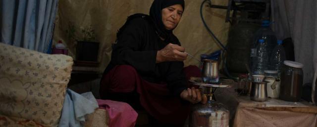 Imm prépare du café dans sa cuisine de fortune, sous sa tente plantée aux abords du village 111, au nord de la plaine de la Bekaa, dans l'est du Liban, à 30 km des frontières syriennes. Crédit : Adrian Hartrick / Oxfam