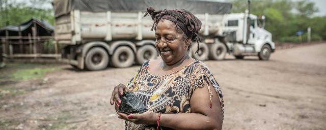 Eneida Díaz holds a piece of coal next to a transport truck.The new mine has polluted the air and land. It has also diverted, contaminated and dried water sources. Communities  have lost their livelihoods and have been displaced. Credit: Pablo Tosco / Oxfam Intermón