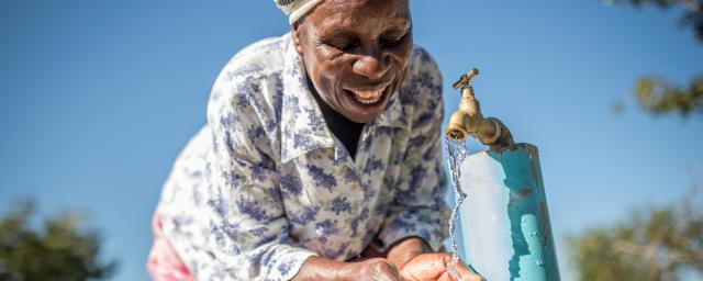 Emmily (65yrs) drinks at a water point in Mabondo village, Masvingo District, Zimbabwe.