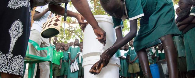 A student of the Primary Complex School in Gondokoro island, South Sudan, washes her hands during an awareness event organised by Oxfam to prevent cholera and inform about good hygiene practices.