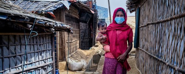 Nur Jahan* with her daughter Ismat* is walking through the narrow alley beside her tent. Rohingya refygee camp. Cox's Bazar, Bangladesh