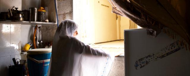 Najwa*, 48, is standing in her partially damaged kitchen in Harasta, Eastern Ghouta, Rural Damascus.