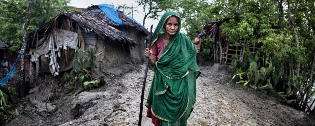 Zohora, 92, walks along a muddy road in Kholpetuya village, searching for food for her grandchildren.