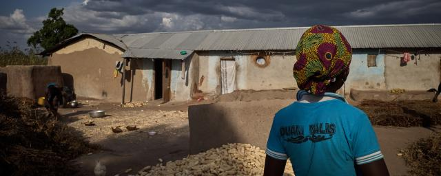 Amaasom walks past corn being dried on their compound whilst the rains threaten to fall.
