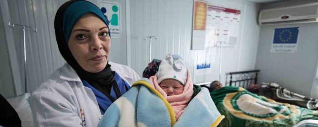 A doctor holds a new born baby, Za'atari Refugee Camp, Jordan