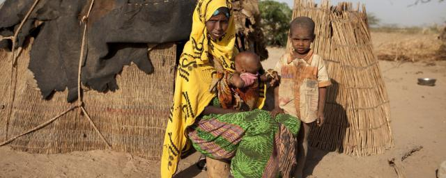 Habodo outside her shelter with two of her children, Habiiba* (3 ½ months) and Saafi* (6), near Bisle, Siti Zone, Somali region, Ethiopia.