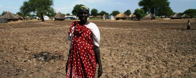 A farmer stands on her prepared land in South Sudan