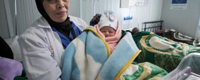 Une femme médecin tenant un nouveau-né dans le camp de Zaatari, en Jordanie.