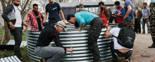 Technical volunteers erect a T11 water tank with a capacity of 11,000 liters of clean drinking water