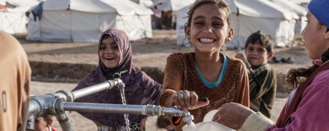 Des enfants remplissent des bouteilles à un point d'eau potable dans le camp de Hassansham, à 50 km à l'est de Mossoul. Crédit: Tegid Cartwright/Oxfam