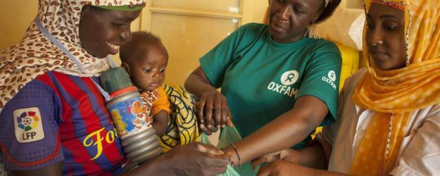A mother and her child who's suffering with malnutrition, receive a hygiene kit. Kits and practice of good hygiene can reduce treatment duration for a child with moderate malnutrition from four to two weeks. Photo credit: Abbie Trayler-Smith/Oxfam