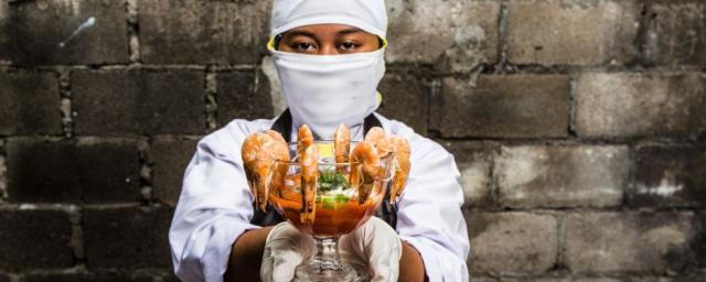 Melati, 18,  worked in an Indonesian shrimp factory. She was expected to peel 600 shrimps an hour. When cleaning the conveyor belt with a chlorine mixture, she burned her hands because she was not given the proper safety equipment. Photo: Adrian Mulya.