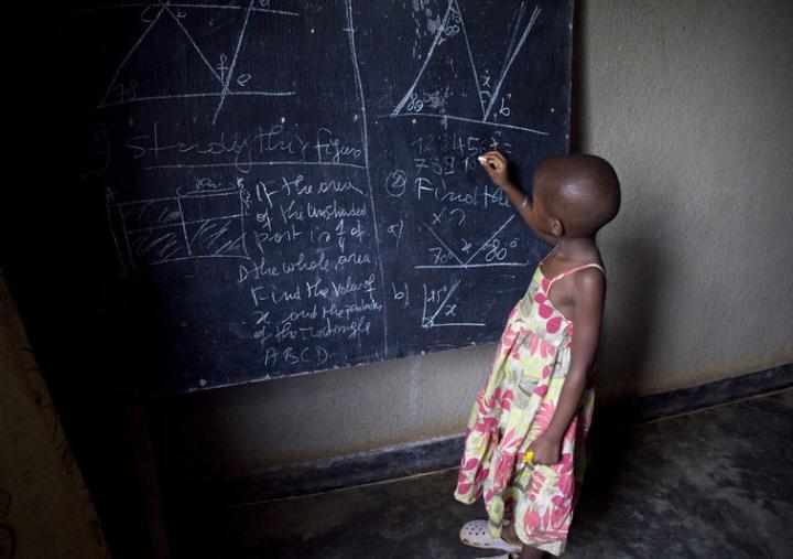 Ecolière devant un tableau noir dans une salle de classe de Kigali, Rwanda. Photo : Simon Rawles
