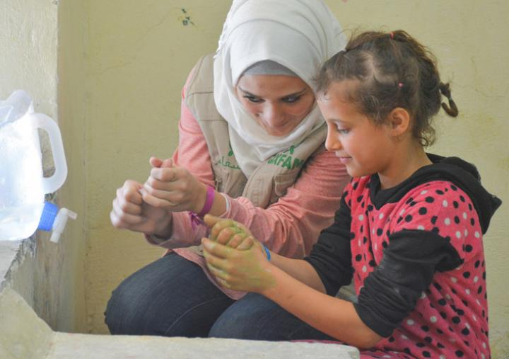 Sana, an Oxfam volunteer in Aleppo, shows children from Aleppo how to wash their hands properly. Nearly 500 children were displaced from Aleppo with their families and returned to the city. Credit: Islam Mardini/Oxfam