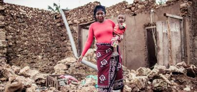 Fatuma walks with her son through her destroyed house after Cyclone Kenneth.